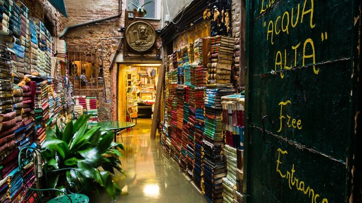 "Libreria Acqua Alta, Venice: Translating as 'high water bookshop', its canalside spot means an extra level of organisation for staff: the rubber boot-wearing owner has to move his books from the floor to bathtubs and higher shelves during regular flooding. ""When Venice is flooded. People are wading along the streets in a foot or two of water & the buildings are boarded up. But the Libreria Acqua Alta is still open for business."