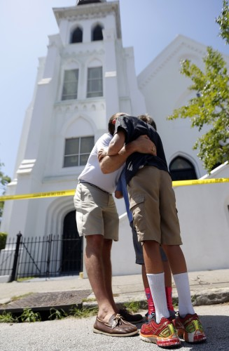 Aaron Eller and his sons Graham and Liam pray, Thursday, June 18, 2015 in front of the Emanuel AME Church in Charleston, S.C. Shooting suspect Dylann Storm Roof, 21, who killed several people including the church pastor, was captured without resistance in North Carolina Thursday after an all-night manhunt, Charleston's Police chief Greg Mullen said. (AP Photo/Stephen B. Morton)