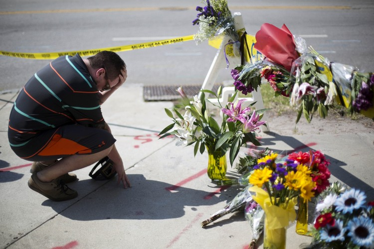 Noah Nicolaisen, of Charleston, S.C., kneels at a makeshift memorial, Thursday, June 18, 2015, down the street from where a man opened fire Wednesday night during a prayer meeting inside the Emanuel AME Church, killing several people in what authorities are calling a hate crime. (AP Photo/David Goldman) ORG XMIT: MIN2015061813574350