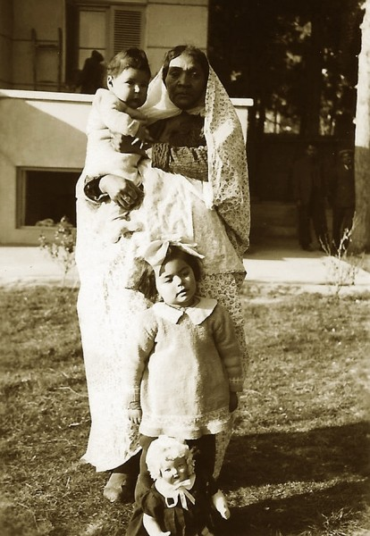 Kamran Afshar in the arms of his nanny, Naneh Sonbol Baji, and Haleh Afshar, standing behind a doll, in Tehran, 1940s. Sonbol Baji, who was of African extraction, was born in a harem and freed in childhood from the court of the last Qajar king, Ahmad Shah (1898-1930). She moved to the home of her future host family, the Afshars, where she grew up, married, and raised her son. She remained there until the end of her life. Photograph: Courtesy of Kamran Afshar