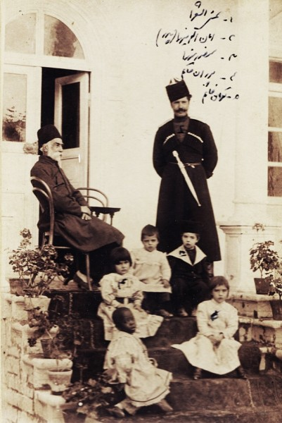 Shams al-Sho'ara (Abdulhossein Mirza Shams Molkara), seated, his son-in-law Amanullah Mirza Jahanbani (1869-1912) standing on the right, small boy wearing a hat (Mansour Mirza Jahanbani), two little girls (Pouran Khanom Jahanbani, Touman Khanom Jahanbani), and an African slave girl, 1900s. Photograph: Modern Conflict Archive, London, UK