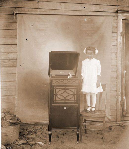 A smiling, unidentified little girl stands on a chair beside a brand new Edison C-150 Sheraton design phonograph. The machine was introduced in June 1915 and was very popular. It became Edison's second-best seller in 1917 and was manufactured until 1918